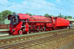 """The Red Devil in 1982: SOUTH AFRICAN RAILWAYS CLASS 25 CONDENSING LOCO MODIFIED TO IDEAS OF ANDRE CHAPELON WITH """" PRODUCER GAS FIREBOX """". PITY IDEA WASN'T TRIED 50 YEARS EARLIER BEFORE DIESELS. TOO POWERFUL FOR HER WHEEL ARRANGEMENT-----TROUBLE WITH SLIPPING AT START."""