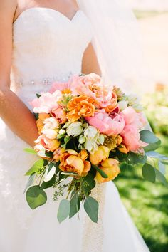 The bridal bouquet will be a slight cascade of coral peonies, seeded eucalyptus, green hydrangeas, pinky orange roses, pinky coral spray roses, pink sweet peas, and coral peonies wrapped in navy ribbon with the stems showing.