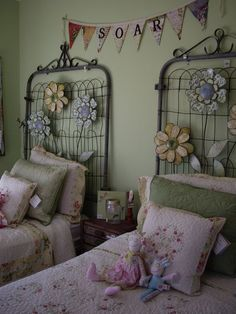 Headboards from garden gates - so cute decorated in spring theme! I think I'd be tempted to paint them white if the wall was dark enough) #garden #gate #headboard #bed #spring #decor #upcycle #repurpose #flowers #kids #bedroom #girls -Reminds me of Mother-in-laws flowers mounted over bed!