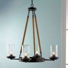 """Suspended by rope-wrapped rods and rigged with clear glass cylinder shades (included), this 4 light chandelier pairs warmly with coastal kitchens and rustic family rooms. 4x60 watts (medium base sockets). (41.25""""Hx29.5""""W)Hurricane glass: 4""""Wx7.5""""H"""