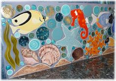 Hand made tiles for a back splash with various sea life: shells, starfish, seahorse and fish