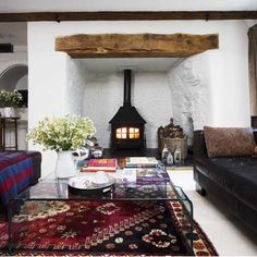 I really like the feature timber plank (I'm sure there is a better way to describe it !) and the rug. Not sure about the glass coffee table but I like the openness and the space around the fire . The white also lifts the darker colours .