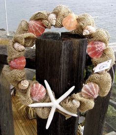 Pretty burlap coastal home wreath with pretty pink, orange and coral pectin shells placed amid folds of burlap netting.