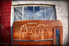 A rusty 10 cent Coke machine sits in front of an Abandoned Phillips 66 gas station in Adrian, Texas, the exact midpoint of old Route 66. From here it's 1,139 miles east to Chicago and 1,139 miles west to Santa Monica.