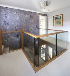 A centrally-positioned oak and glass staircase with a half-landing turn and gallery landing.