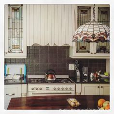 Country kitchen with stained glass Tiffany style chandelier and matching stained glass cabinets