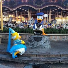 Daisy watching Donald try and pull the sword in front of Cinderella's carousel Walt Disney World