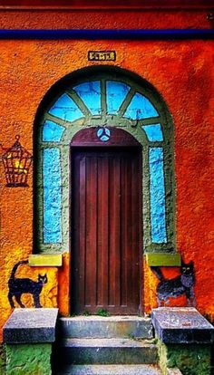 Medellín, Colombia ~ The color of the house really brings out the turquoise color of the door. Not sure if the 'cats' are placed there to scare people away, or not.