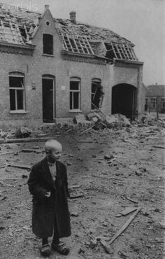 A Dutch boy stands alongside a building badly damaged by the war, 1944.
