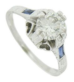 This spectacular Art Deco engagement ring features a gorgeous 1.04 carat, H-I color, Si2 clarity round cut diamond. A pair of baguette cut sapphires stretch along the rings shoulders. Elongated prongs reach from the sides of the mounting, while abstract floral engraving decorates the sides and shoulders of the ring. Bold cutwork hearts slice into the domed sides of the mounting. The antique ring is fashioned of 18K white gold and measures 9.90 mm in width. Circa: 1920. Size 7 1/4, domed.