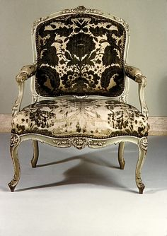 Retro style worn velvet armchair with gold carved detail in the arms and legs
