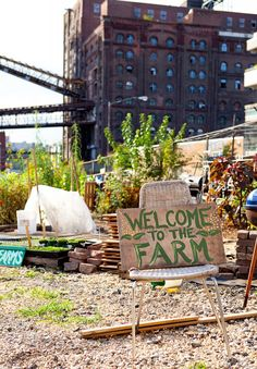 Love the contrast of the garden with the Industrial building in the background.    North Brooklyn Farms welcome sign l Gardenista