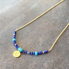 """""""Om"""" charm necklace with lapis, turquoise and gold. By Stone Poetry."""