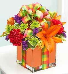 Send a present from nature; a fresh bouquet of orange lilies, vibrant carnations, poms and more, beautifully hand-created in a chic cube vase lined with an orange foam ribbon. Meant to resemble a stylish gift box, this arrangement is perfect for birthdays, anniversaries or a thinking of you surprise. Our designers select the freshest flowers available so floral colors and varieties may vary.  #denverflorist #denverflowers #denverflowerdelivery
