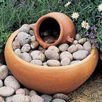 Easy to make water feature Bubbling Urn: Materials needed include a water feature urn, large terracotta pan, pond pump, plastic-coated grille, pond liner, cobbles, hose and bricks