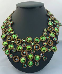 A stunning statement necklace made by Damnedhalo using the new Swarovski Elements in Scarabaeus Green - a fabulous collaboration with the wondrous mind of Jean-Paul Gaultier. It is comprised of 14mm rivolis, 8mm chatons and 2mm montees, all in Scarabaeus Green. Each Swarovski Element is hand bezelled in golden olive iris precision Japanese Delicas and tiny size 15 seed beads and sewn to its neighbours securely to make this one of a kind necklace. Sitting at the base of the throat, and…