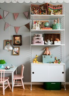"""Här till höger utnyttjas ytan ända upp till tak för att göra det mer ombonat. Bården som ger lite cirkuskänsla kommer från Eco Wallpaper. Vimpel, Numero 74. Stringhylla, Länna Möbler. Tavlor, Mokkasin. Lampa """"Flower Pot"""", & Tradition. Maten har barnens faster virkat. Tårtfat, H&M Home. Servis, bord och stolar, second hand.  I hyllan: Resväskor, Miniroom. Träleksaker, Molly Meg. Dragdjur, Brio och mockasiner, Minimocks. Resten köpt på loppis."""
