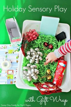 Holiday Gift Wrap Sensory Bin. Tons of fun plus fine motor and cutting practice for a holiday theme in your preschool classroom!