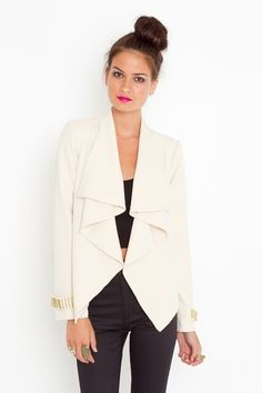 Chic structured cream jacket featuring an ultra-drapey collar and asymmetric hem. Gold bar detail at cuff and back