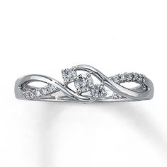 A gentle wave of round diamonds is elegantly offset by double swirls of 10K white gold in this delightful promise ring for her. Three additional diamonds lend even more brilliance to the center of this ring containing a total diamond weight of 1/5 carat.