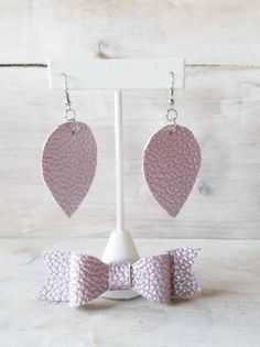 This is part of our Mommy and Me collection. The bow and earrings are made with Faux Leather in a Lavender Color with a White Backing.  The Earrings and Bow are lightweight, and easy to wear.  Each bow comes with a choice of an alligator clip, or a nylon headband that is one size
