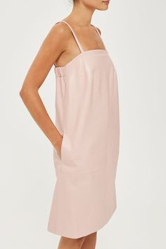 In butter-soft pink leather, this directional slip dress courtesy of Boutique will ensure you make a style statement. Falling to the knee, this loose fitting style features a square neckline, a stretch hem in the back and two subtle side pockets. Complete this look with contrast leather mules and a wrist cuff. Made in Britain.