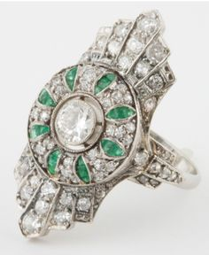 Art Deco Diamond and Emerald Ring. Splendid Diamond and Emerald ring exemplifying the beauty of the Art Deco era. Center Diamond weighs approximately 0.40 carats. The rest of the Diamonds weigh approximately 1 carat. Accented by Emeralds. Via 1stdibs.