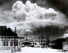 AUG. 9, 1945  The exact moment of detonation at Nagasaki is captured in this remarkable photograph. Notice the three people in the foreground, as yet unaware that anything has happened. The destruction of Nagasaki followed that of Hiroshima by three days and compelled Japan to surrender, ending World War II.