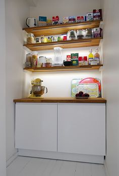 open shelving under shelf lights, or back lit. Could hide washer dryer, counter top folds up for the top load washer.