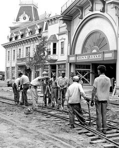 Workers lay the foundation of the trolley tracks along Main Street. Horse-drawn streetcars travel on these tracks today, going between Town Square and Sleeping Beauty Castle.