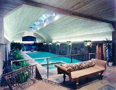 Indoor swimming pool using China Lotus slate flooring and granite coping.... Illuminated pyramid bush hammered columns provide a base for the large illuminated urns...