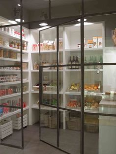 Walk-in pantry features metal and glass door opening to built-in pantry shelves illuminated by industrial sconces.