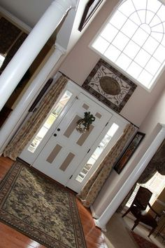 Floor to ceiling curtains on both sides of entry door.  Two Story Foyer - traditional - entry - dc metro - Savvy Seasons