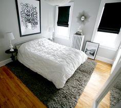 pale grey walls, framed poster above bed. black blind. Katie Kirk grey bedroom - design sponge