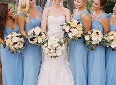 Blue bridesmaids dresses with lush cream bouquets