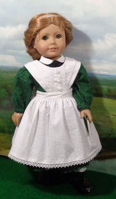 Mid 1800s Green School Dress with Pinafore for 18 inch Girls. The long sleeves on this dress have machine embroidery on the cuffs which close with button covered snaps. The white on white pinafore has a lined bib and bretelles at the shoulders. It closes in back with white sash ties from the waistband. Dress, pinafore, pantalettes and book.