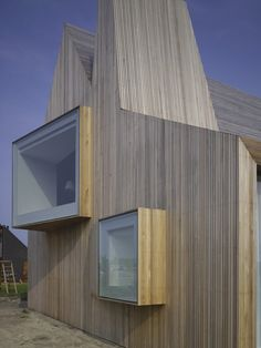 Dutch timber-clad house featuring different shaped windows on all sides