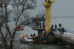 Russian rescue workers collect wreckage from the crashed plane at a pier just outside Soch...