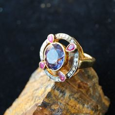Eye catching Ring made of everything that is good in the world. A large round cut amethyst is set in the middle if the setting appearing to be suspended by four rubys from the circle of diamonds. This