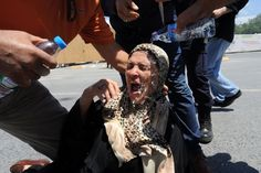 Protesters pour water on a woman's head after she fell to the ground on June 1, 2013 during clashes with riot police against the demolition of Taksim Gezi Park in Istanbul