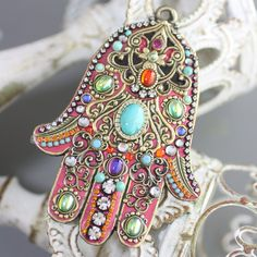 A bright and chic wall hamsa (4.5 inches) decorated with enamel, crystals and featuring an African turquoise in the center. A modern reinterpretation of a ubiquitous middle eastern cultural theme, this piece looks great mounted on walls and doorways. Features a soldered mounting ring for easy placement.
