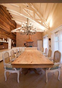 """A ideia era ter uma cozinha gourmet para receber, sentar e comer, como numa grande casa de fazenda. A sala de jantar é limitada por um volume de Limestone Mont Dorê (Pedras de Esquina Marmoraria) com cooktop, cercado de armários da linha Vintage (branco """"offwhite""""), da Ornare, cujo tampo serve como apoio. A mesa de jantar em pinus é da Micasa e as cadeiras Provance Novoantigo, têm acabamento em pátina branca. O projeto arquitetônico da casa no interior paulista é de Maurício Karam"""