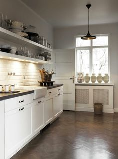 gorgeous wood herringbone floor with white tile and cabinets.