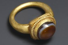 A RING WITH AGATE INLAY D. 2 cm. Gold, banded agate Roman, 2nd-3rd cent. A.D.
