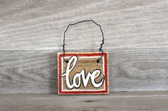 Share the love with a friend or loved one with this hand-painted wood sign. It can be used as a door hanger or on a wall. The door hanger is made with