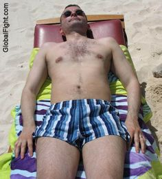 a cubby man beach resort sand suntanning wet oily