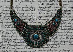 Collier de type plastron vert/bleu/rose, composé de 3 belles pièces articulées en métal doré vieilli, rehaussées de petits cabochons, perles, céramique, fils synthétiques et strass. Au centre 1 joli palet rond en céramique bleue craquelé.