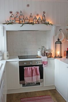 Christmas decorations in a white Scandinavian kitchen featuring gingerbread houses with big windows and lit from the back