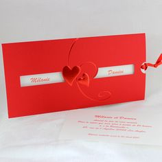 Faire-part de mariage Jakarta   Vous recherchez un faire-part de mariage reflétant votre amour et votre passion l'un pour l'autre ? Ne cherchez plus. Pochette rectangulaire, en plike rouge, coeurs gaufrés et métallisés rouge. Une fenêtre fait apparaitre vos prénoms. L'encart et la carte d'invitation ivoire sont maintenus ensemble par un fin ruban satin rouge.