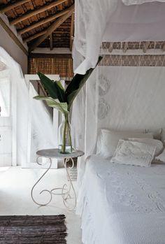 """A florista Karin Farah decorou sua suíte em Trancoso (BA) com ares de casinha simples de pescador. """"Queríamos uma combinação de natureza e simplicidade, mas também certo toque de sofisticação e elegância"""", conta. Por isso, a opção pelo branco e pelas rendas – estas, encomendadas com rendeiras locais. Sobre a grande cama box de 2,60 x 2,60 m, há um delicado dossel. Os tapetes de bambu são obra dos índios pataxós."""
